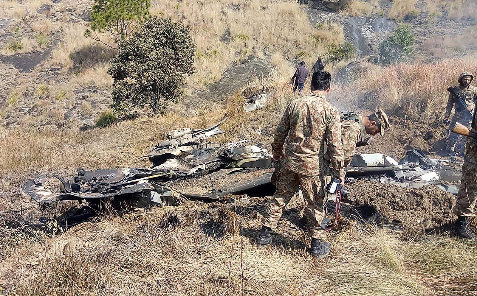 پاک فوج کے جوان تباہ حال بھارتی طیارے کے ملبے کا جائزہ لے رہے ہیں۔ فوٹو: اے ایف پی