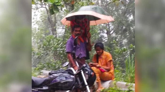 تیز بارش میں بیٹی کو فٹ پاتھ پر آن لائن کلاس دلواتا والد سوشل میڈیا پر مقبول
