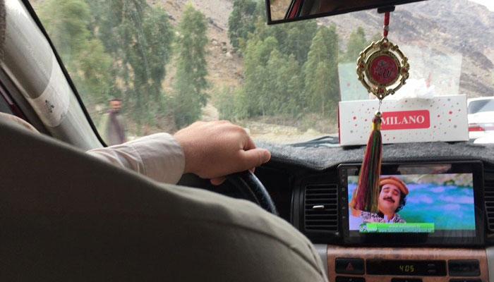پشتون ڈرائیو ر نے جھجھکتے ہوئے گانے چلانے کا پوچھا اور ٹیپ آن کردیا ہے —فوٹو: قسیم سعید